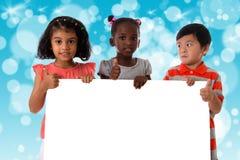 Ομάδα πολυφυλετικού πορτρέτου παιδιών με το λευκό πίνακα στοκ εικόνες