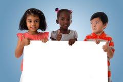 Ομάδα πολυφυλετικού πορτρέτου παιδιών με το λευκό πίνακα στοκ εικόνα με δικαίωμα ελεύθερης χρήσης