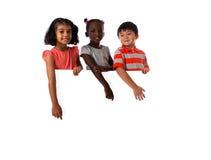 Ομάδα πολυφυλετικού πορτρέτου παιδιών στο στούντιο με το λευκό πίνακα απομονωμένος στοκ εικόνες