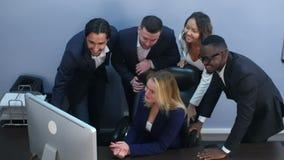 Ομάδα πολυφυλετικών επιχειρηματιών που εξετάζουν μια οθόνη του lap-top, που έχει την τηλεδιάσκεψη απόθεμα βίντεο