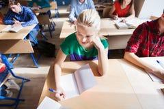 Ομάδα σπουδαστών με τα βιβλία που γράφουν τη σχολική δοκιμή Στοκ Φωτογραφίες