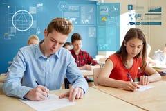 Ομάδα σπουδαστών με τα βιβλία που γράφουν τη σχολική δοκιμή Στοκ φωτογραφία με δικαίωμα ελεύθερης χρήσης