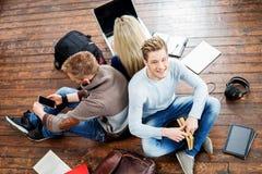 Ομάδα σπουδαστών που διαβάζουν τα βιβλία, που γράφει στα σημειωματάρια Στοκ Εικόνα
