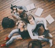 Ομάδα σπουδαστών που διαβάζουν τα βιβλία, που γράφει στα σημειωματάρια Στοκ Εικόνες