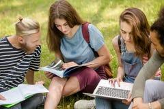 Ομάδα σπουδαστών που κάθονται στη μελέτη χλόης Στοκ φωτογραφία με δικαίωμα ελεύθερης χρήσης