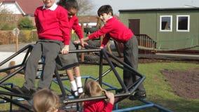 Ομάδα στοιχειωδών παιδιών σχολείου στο πλαίσιο αναρρίχησης φιλμ μικρού μήκους