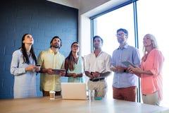 Ομάδα συναδέλφων χρησιμοποιώντας τα lap-top και smartphones και ανατρέχοντας στοκ φωτογραφίες