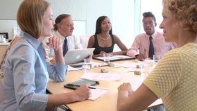 Ομάδα συνεδρίασης του Businesspeople γύρω από το γραφείο στην αρχή απόθεμα βίντεο