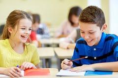Ομάδα σχολικών παιδιών που γράφουν τη δοκιμή στην τάξη στοκ φωτογραφίες