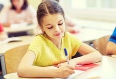 Ομάδα σχολικών παιδιών που γράφουν τη δοκιμή στην τάξη στοκ φωτογραφία