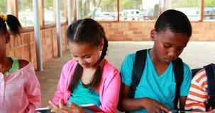 Ομάδα σχολικών παιδιών που χρησιμοποιούν την ψηφιακά ταμπλέτα και το lap-top στην πανεπιστημιούπολη φιλμ μικρού μήκους