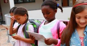 Ομάδα σχολικών παιδιών που χρησιμοποιούν την ψηφιακή ταμπλέτα και το κινητό τηλέφωνο απόθεμα βίντεο