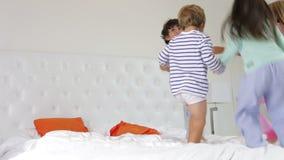 Ομάδα τέσσερα παιχνίδι παιδιών δαχτυλίδι-γύρω από-ο-ροδοειδές στο κρεβάτι γονέων απόθεμα βίντεο