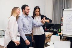 Ομάδα τεσσάρων διαφορετικών εύθυμων συναδέλφων που παίρνουν την αυτοπροσωπογραφία και που κάνουν τις αστείες χειρονομίες με τα χέ Στοκ φωτογραφία με δικαίωμα ελεύθερης χρήσης