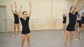 Ομάδα τεσσάρων νέων ballerinas που στέκεται στο μπαλέτο σειρών και άσκησης απόθεμα βίντεο