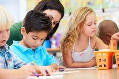 Ομάδα του δημοτικού σχολείου παιδιών ηλικίας στην κατηγορία τέχνης με το δάσκαλο Στοκ Εικόνες