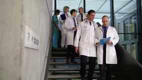 Ομάδα των γιατρών που αλληλεπιδρούν περπατώντας κάτω από τα σκαλοπάτια απόθεμα βίντεο