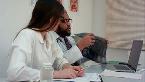 Ομάδα των γιατρών που εξηγούν τα των ακτίνων X αποτελέσματα στον ασθενή μέσω της τηλεοπτικής κλήσης απόθεμα βίντεο