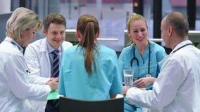 Ομάδα των γιατρών που διοργανώνουν μια συνεδρίαση στη αίθουσα συνδιαλέξεων απόθεμα βίντεο