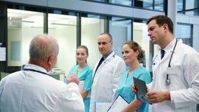 Ομάδα των γιατρών που διοργανώνουν μια συνεδρίαση στο διάδρομο φιλμ μικρού μήκους