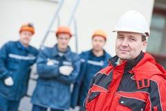 Ομάδα των τεχνικών εργατών οικοδομών με τον επιστάτη στο μέτωπο στοκ εικόνες
