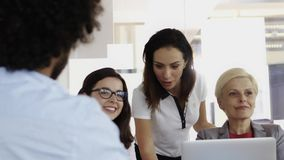 Ομάδα των υπαλλήλων που εργάζονται στον υπολογιστή μαζί στο γραφείο τους απόθεμα βίντεο