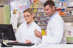 Ομάδα των φαρμακοποιών που εξετάζουν τον υπολογιστή στοκ εικόνα