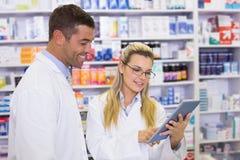Ομάδα των φαρμακοποιών που εξετάζουν το lap-top στοκ φωτογραφία