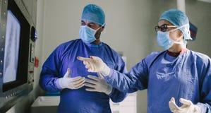 Ομάδα των χειρούργων που χρησιμοποιούν τη νέα τεχνολογία στη χειρουργική επέμβαση στοκ εικόνες