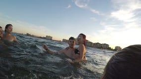 Ομάδα φίλων που έχουν τη διασκέδαση στη θάλασσα - κυματισμός και που λένε γειά σου απόθεμα βίντεο