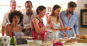 Ομάδα φίλων που επιλέγουν τα τρόφιμα από τον μπουφέ κόμματος στο σπίτι απόθεμα βίντεο