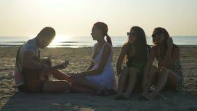 Ομάδα φίλων που κάθονται σε μια παραλία και που τραγουδούν με μια κιθάρα απόθεμα βίντεο