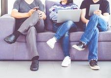 Ομάδα φίλων που κάθονται στο βήχα και που έχουν τη διασκέδαση και που χρησιμοποιούν το ψηφίο Στοκ Εικόνες