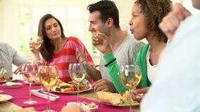 Ομάδα φίλων που κάθονται τον πίνακα που έχει το κόμμα γευμάτων απόθεμα βίντεο