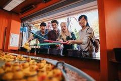 Ομάδα φίλων που παίζουν το παιχνίδι αλιείας στον εκθεσιακό χώρο Στοκ Φωτογραφίες
