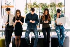 Ομάδα φίλων που στέκονται στον πίνακα και που κοιτάζουν βιαστικά στα divices τους στο σύγχρονο δωμάτιο στοκ φωτογραφία με δικαίωμα ελεύθερης χρήσης