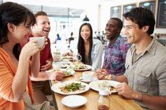Ομάδα φίλων που συναντιούνται για το μεσημεριανό γεύμα στη καφετερία