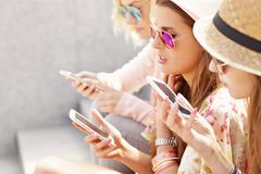 Ομάδα φίλων που χρησιμοποιούν smartphones στην πόλη Στοκ εικόνα με δικαίωμα ελεύθερης χρήσης