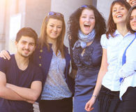 Ομάδα φοιτητών πανεπιστημίου που χαμογελούν τη φιλική στάση το ένα δίπλα στο άλλο, την ηλιόλουστη ημέρα στοκ εικόνα με δικαίωμα ελεύθερης χρήσης