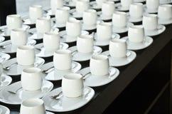 Ομάδα φλυτζανιών καφέ Κενά φλυτζάνια για τον καφέ Πολλές σειρές του άσπρου φλυτζανιού για το τσάι υπηρεσιών ή του καφέ στο πρόγευ Στοκ Φωτογραφία