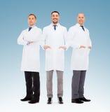 Ομάδα χαμογελώντας αρσενικών γιατρών στα άσπρα παλτά Στοκ Φωτογραφία