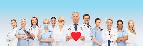 Ομάδα χαμογελώντας γιατρών με την κόκκινη μορφή καρδιών Στοκ Φωτογραφίες