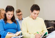 Ομάδα χαμογελώντας σπουδαστών με τα σημειωματάρια Στοκ Φωτογραφίες