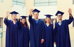Ομάδα χαμογελώντας σπουδαστών στα mortarboards Στοκ Φωτογραφία