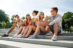 Ομάδα χαμογελώντας φίλων που κάθονται στο τετράγωνο πόλεων Στοκ εικόνα με δικαίωμα ελεύθερης χρήσης