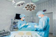 Ομάδα χειρούργων που εργάζεται με τον έλεγχο του ασθενή Στοκ εικόνα με δικαίωμα ελεύθερης χρήσης