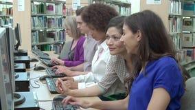 Ομάδα ώριμων σπουδαστών με την εργασία δασκάλων στους υπολογιστές απόθεμα βίντεο