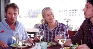 Ομάδα ώριμων φίλων που απολαμβάνουν το γεύμα στο εστιατόριο από κοινού φιλμ μικρού μήκους