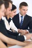 Ομάδα businesspeople ή δικηγόρων που συζητά τα έγγραφα συμβάσεων και οικονομικοί αριθμοί καθμένος στον πίνακα Κινηματογράφηση σε  Στοκ Εικόνα