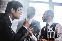 Ομάδα Multiethnic επιχειρηματιών που καπνίζουν και που πίνουν το ουίσκυ στο εσωτερικό Στοκ Φωτογραφίες